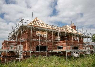 A progress photo of a new build home with timber roof trusses