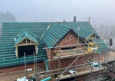 another view of the roof trusses being installed on a home in downham market